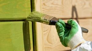 hand met handschoen en schilderskwast met groene verf